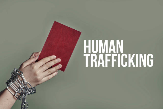 A female hands in chains holding passport - human trafficking