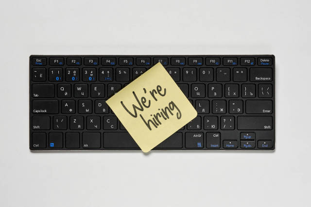 A sticky note on the pc keyboard with We are hiring phrase