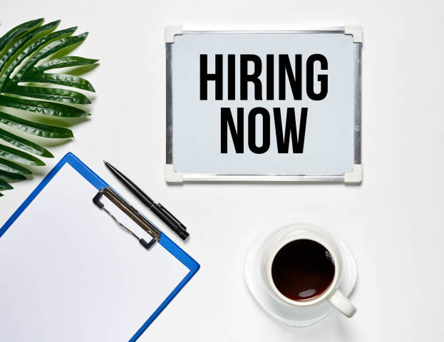 Hiring now concept on bright office workspace background