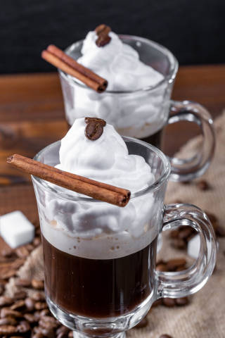 Coffee with whipped cream and cinnamon stic