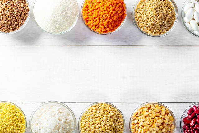 Various cereals in small bowls on a white wooden background with free space