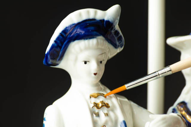 Refreshing the golden paint on a ceramic figurine