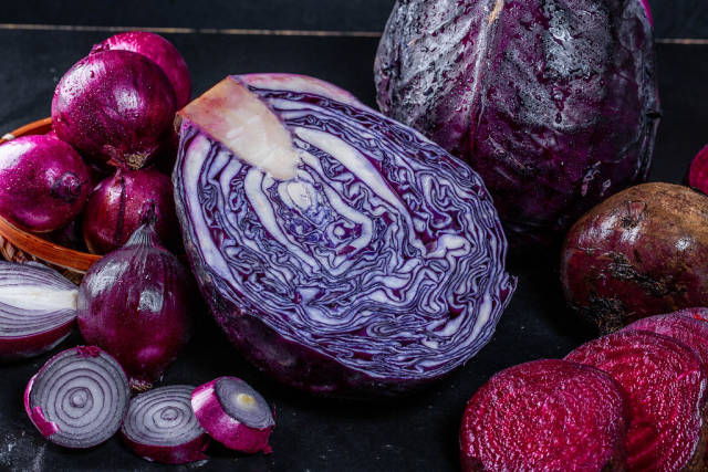 Red cabbage, onions and beets on a dark background