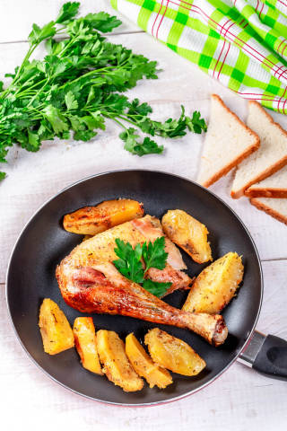 Pan with fried chicken leg and potatoes on a white wooden table with bread and herbs