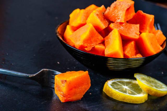 Healthy baked pumpkin dessert with lemon slices and fork on black background
