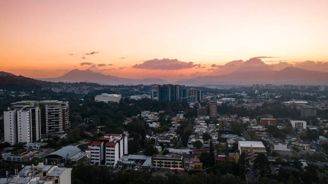 Sunset over Guatemala City Buildings over the Volcanoes on the Horizon