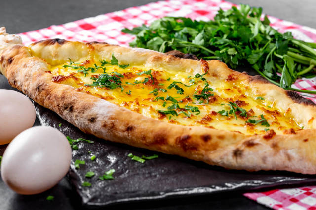 Hot open khachapuri with chicken egg and greens