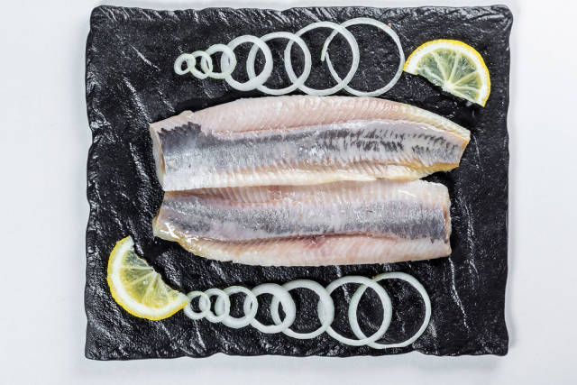 Salted herring with onion slices and lemon slices