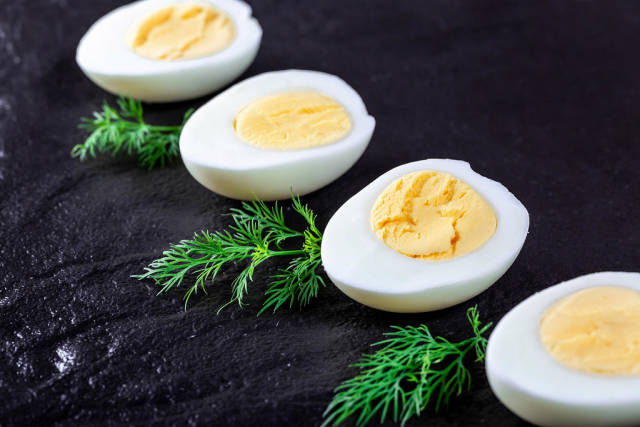 Halves of boiled eggs on a black background with greens