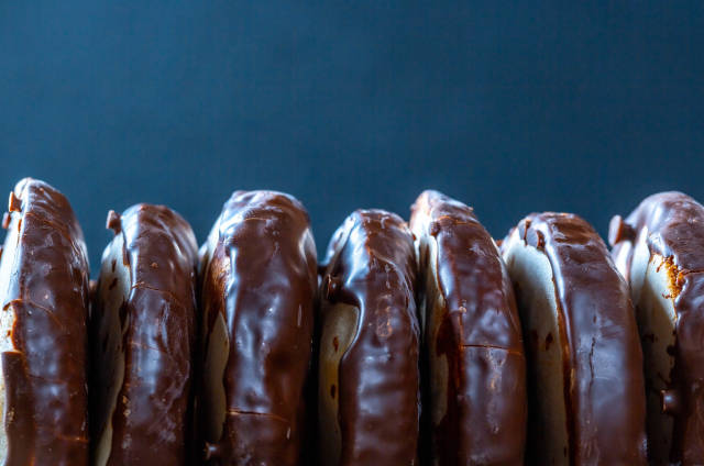 Sweet gingerbread in chocolate icing on a dark background