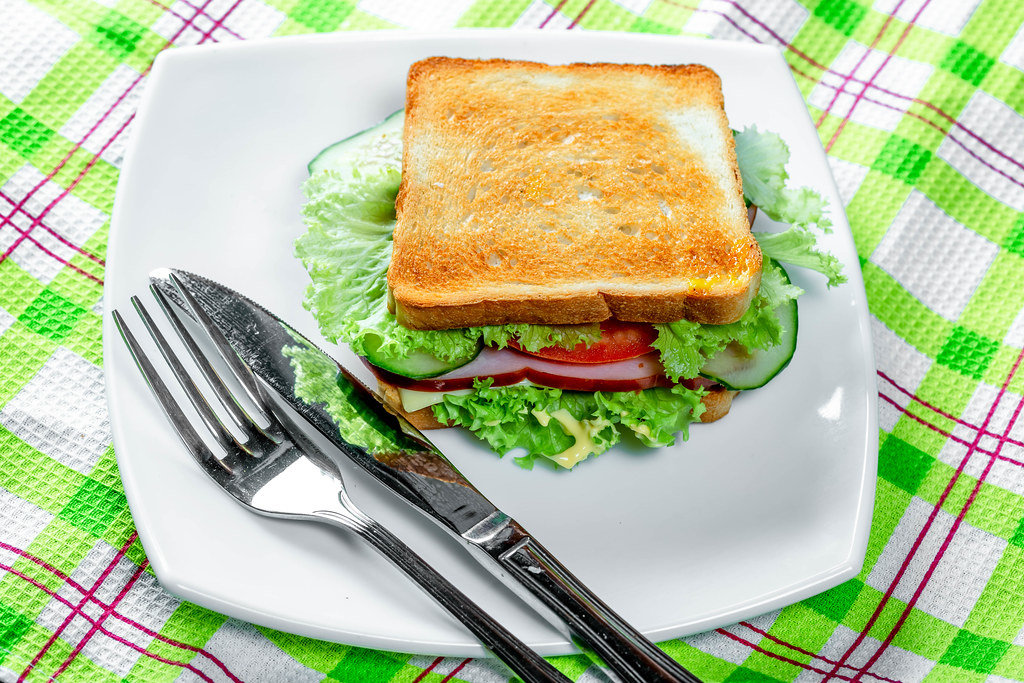 Toast with fried bread, ham and vegetables on a white plate with knife and fork