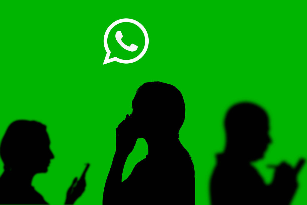 Business people shadows and whatsapp messenger logotype on a large screen