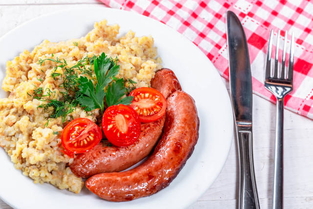 Funny lunch with porridge, sausages, tomatoes and herbs