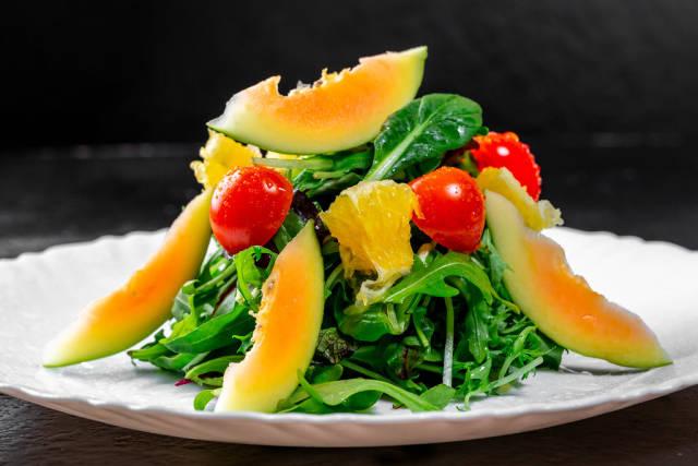 Vegetarian salad with herbs, tomatoes, avocado and orange