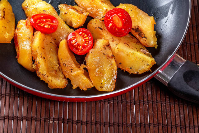 Fried potatoes in a frying pan with cherry tomatoes