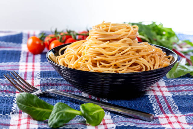 Delicious spaghetti in a black bowl with herbs and tomatoes in the background