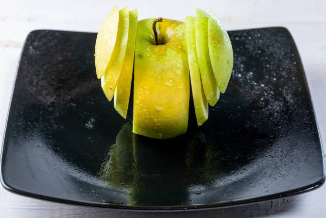 Fresh green Apple sliced on a plate