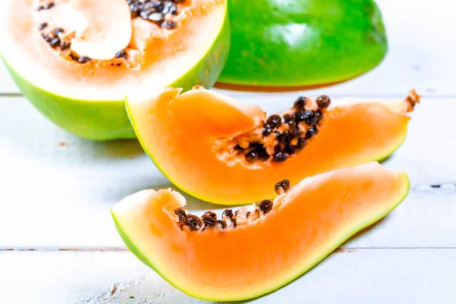 Pieces of fresh ripe papaya on white wooden background