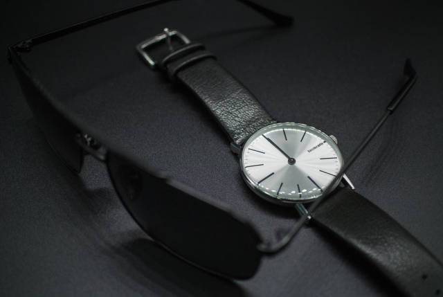 Sunglasses and black leather wristwatch. Formal wear accessories