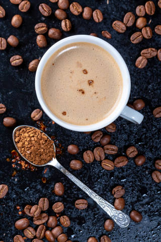 Cup of coffee, ground coffee and beans on dark background. Top view
