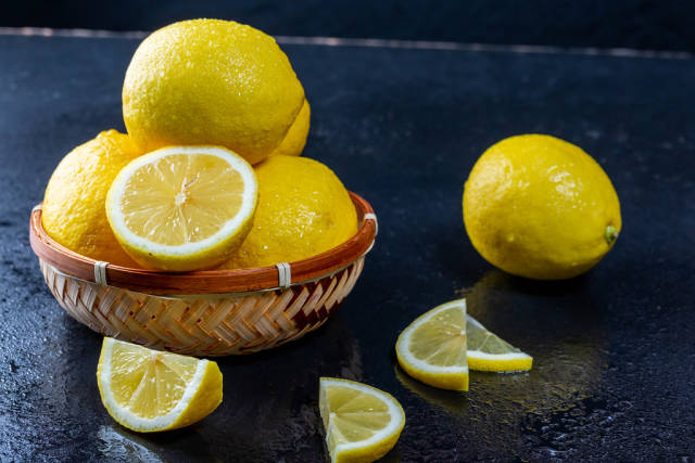Fresh whole and sliced yellow lemons on a dark table