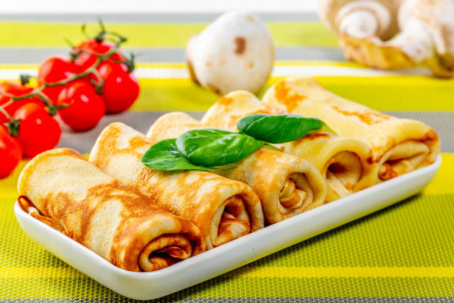 Pancakes with mushrooms and tomatoes on the table