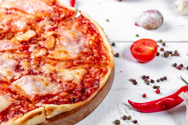 Baked pizza with spices on a white wooden table
