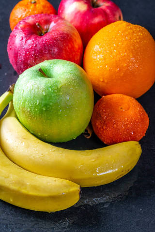Green and red apples, bananas, oranges and tangerines with water drops