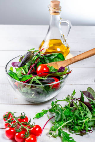 Fresh salad with arugula leaves, spinach, tomatoes and olive oil on a white wooden table