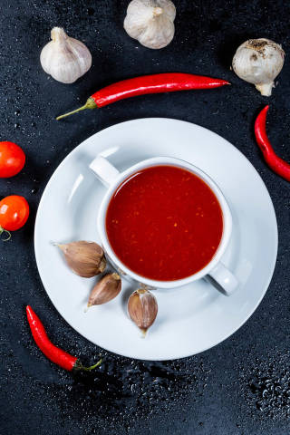 Bowl of fresh homemade tomato soup and spice on black table, top view