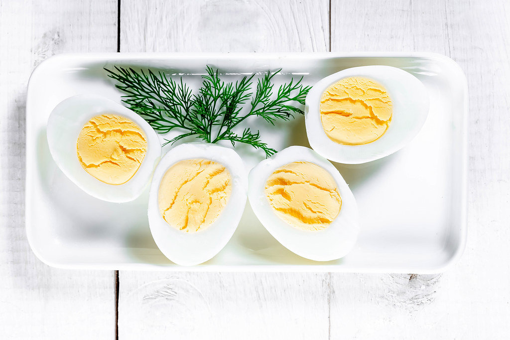 Boiled eggs cut on a plate with dill leaves on a white wooden background