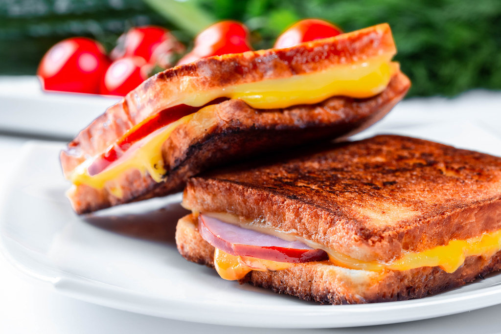 Two fried on grilled sandwiches with cheese and ham