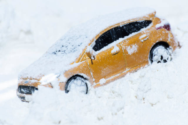 A yellow family car is standing on a snowy road