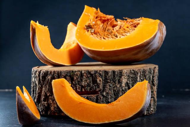 Pieces of ripe orange pumpkin on a wooden stump