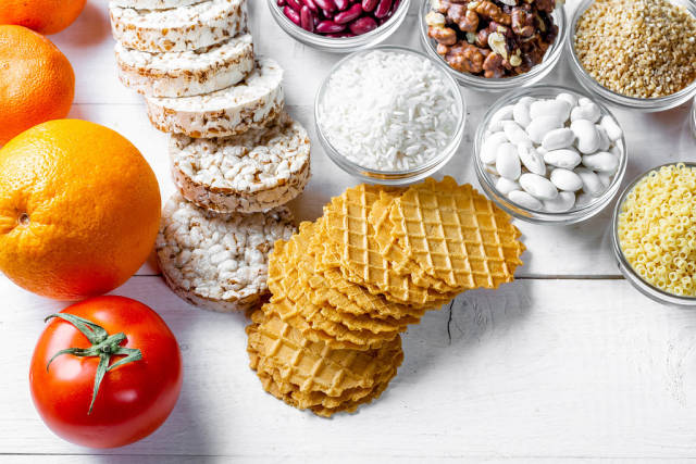 Fruits, cereals, loaves, walnuts on white wooden background