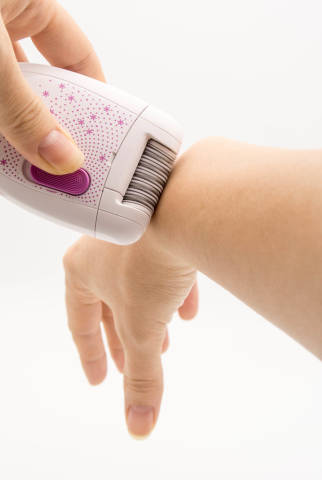 Woman removing hair from her arm with an epilator