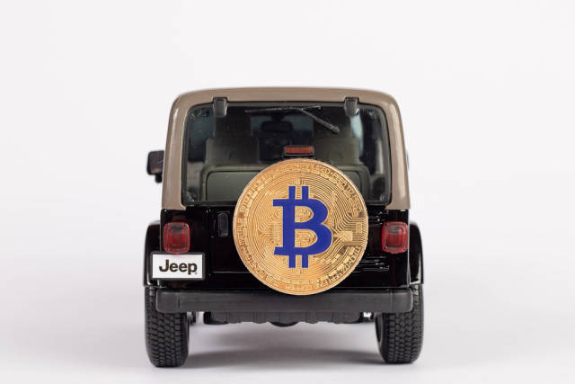 Black SUV car carrying Bitcoin on the back of the car