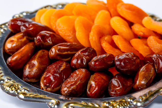 Tray with dried dates and dried apricots close-up