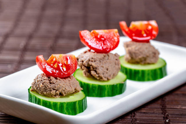 A light snack with cucumbers, liver pate and slices of cherry tomatoes