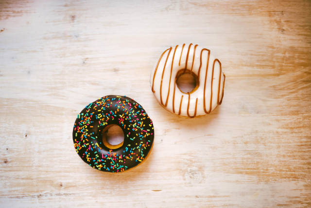 Sweet donuts on white wooden background