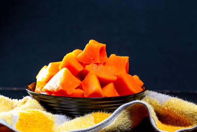 Pieces of baked pumpkin in a black bowl with a kitchen towel