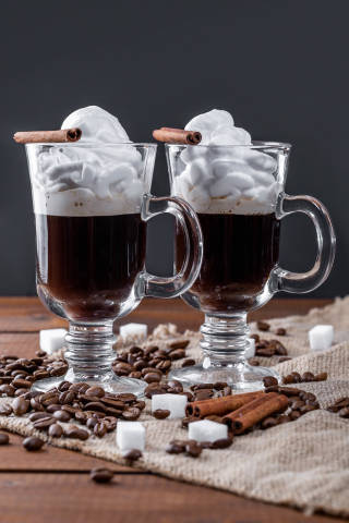 Coffee with cream, cinnamon sticks, sugar cubes, spices and coffee beans on a wooden table