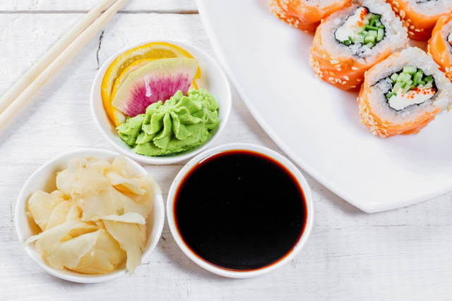 Pickled ginger, soy sauce and wasabi sauce in white saucers and sushi