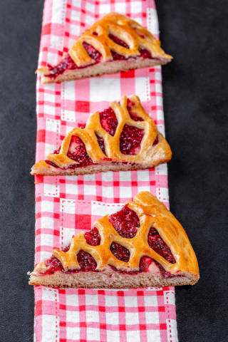 Sliced pieces of cake with raspberry jam on a dark background