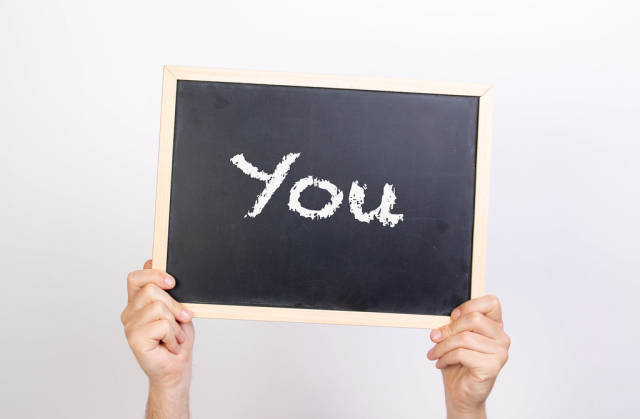 Hands holding blackboard with text You