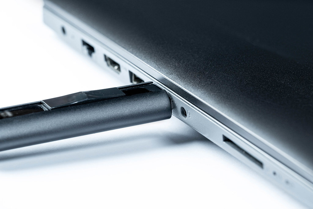 Flash memory drive plugged into a laptop port.