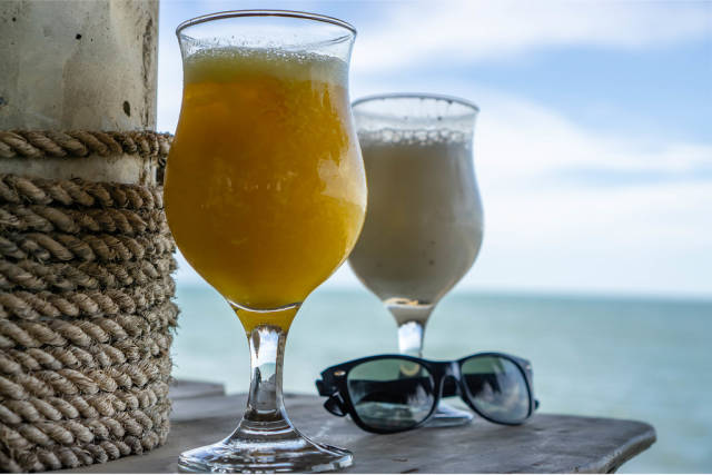 Cocktails and Sunglasses on a Table with Seaview in the Background