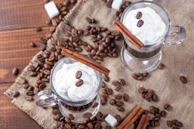 Top view of coffee with cream, coffee beans and spices on burlap