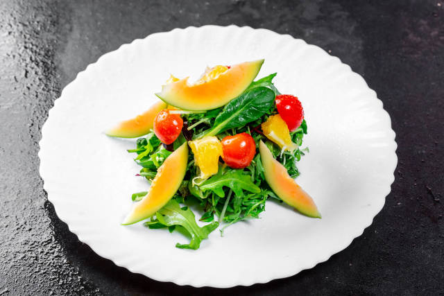 Salad with fresh avocado, cherry tomatoes, orange slices and arugula leaves