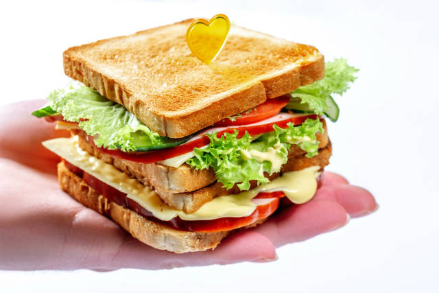 Appetizing sandwich with lettuce, tomatoes, cheese and ham on the mans hand